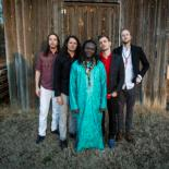 Diali Cissokho stands in front of a barn at the center as his two bandmates stand on either side