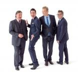 Greg Proops, Jeff B. Davis, and Joel Murray jumping in the air while Ryan Styles remains standing.