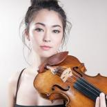 A musician is standing and facing the camera while she holds a violin prepared to play
