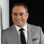 Gilberto Santa Rosa is wearing a grey suite and black tie as he stands against a wall
