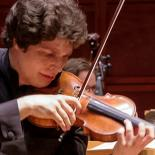 Artist Augustin Hadelich stands in the forefront as he plays violin with other musicians behind him