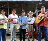 five men standing together holding bluegrass instruments looking directly at the camera