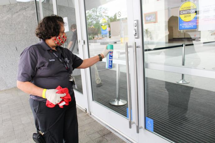 RCC staff member cleaning the door handles of the main entrance.