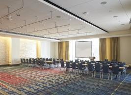 Room arranged in conference style with 6 tables facing podium
