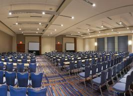 Wide shot of 10 rows of chairs facing projection screens