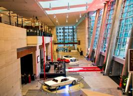 Photo overlooking lobby that has 3 cars parked parked inside with red carpet