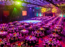 Ballroom full of fancy set tables and colorful lighting for a gala event